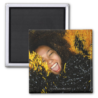 Cheerleader laughing, surrounded by pompoms, magnet