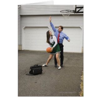 Cheerleader playing basketball with her father card