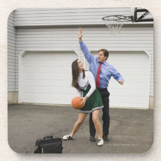 Cheerleader playing basketball with her father coaster