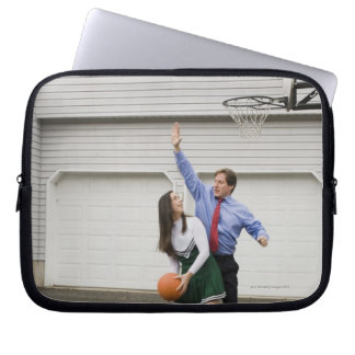 Cheerleader playing basketball with her father laptop sleeve