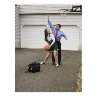 Cheerleader playing basketball with her father postcard
