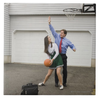 Cheerleader playing basketball with her father tile