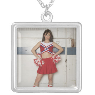 Cheerleader standing on bench near basketballs, silver plated necklace