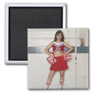 Cheerleader standing on bench near basketballs, square magnet