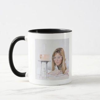 Chemist looking at Bunsen burner Mug