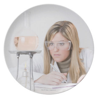 Chemist looking at Bunsen burner Party Plate