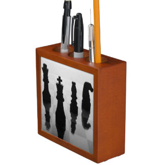 Chess pieces on chess board in black and white desk organiser