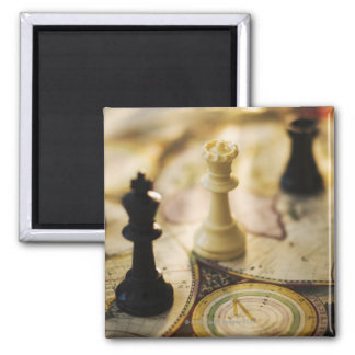 Chess pieces on old world map square magnet