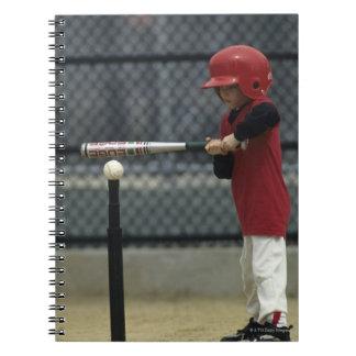 Child batting a tee ball spiral note book