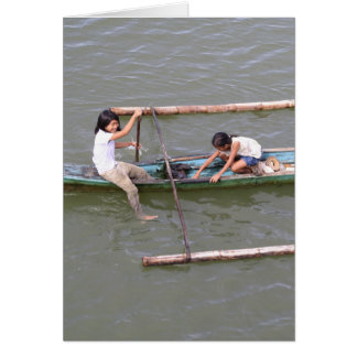 Children playing in a fishing boat greeting card