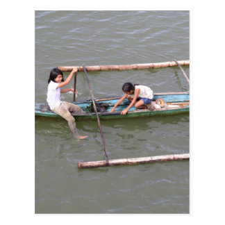 Children playing in a fishing boat postcard