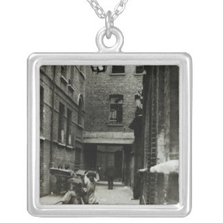 Children playing in a slum, 1899 silver plated necklace