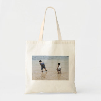 Children playing on the beach budget tote bag