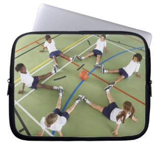 Children sitting on the floor of a sports hall laptop sleeve