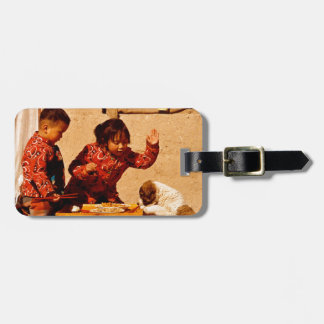 Chinese children playing with a dog tags for luggage