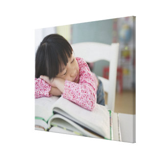 Chinese girl napping on textbooks canvas print