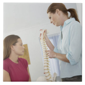 Chiropractor and patient. The chiropractor is Tile