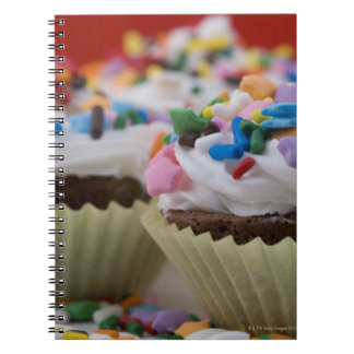 Chocolate cupcakes with icing and sprinkles, notebook