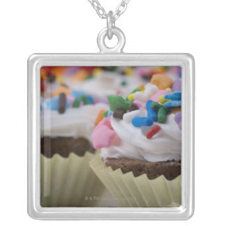 Chocolate cupcakes with icing and sprinkles, silver plated necklace