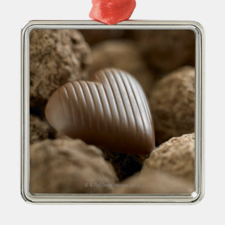 chocolate nestled amongst other chocolates Silver-Colored square decoration