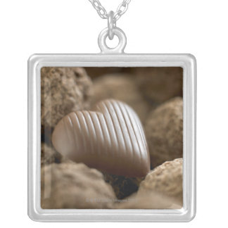 chocolate nestled amongst other chocolates silver plated necklace