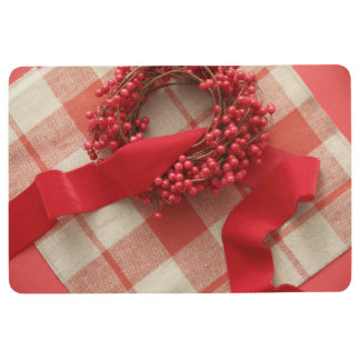 Christmas berries and wreath on plaid floor mat