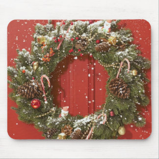 Christmas wreath hanging on a door mouse mat