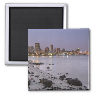 City lights at twilight with debris strewn beach square magnet