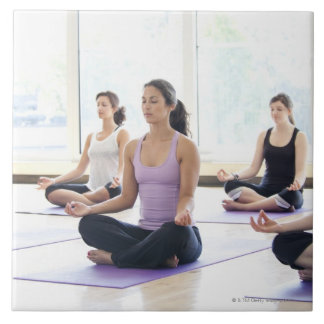 Class of women performing the meditative large square tile