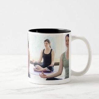 Class of women performing the meditative coffee mug