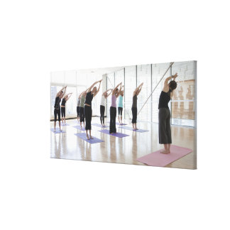 class practicing yoga with instructor in a 2 canvas prints