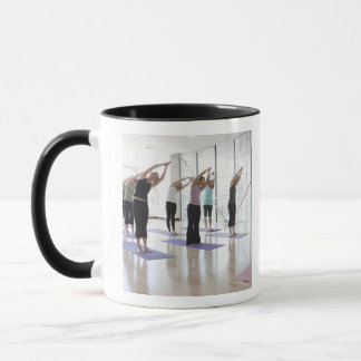 class practicing yoga with instructor in a 2 mug