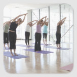 class practicing yoga with instructor in a 2 sticker