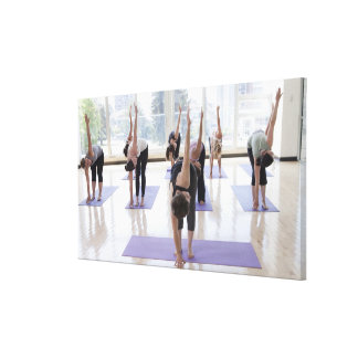class practicing yoga with instructor in a canvas print
