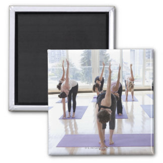 class practicing yoga with instructor in a magnet