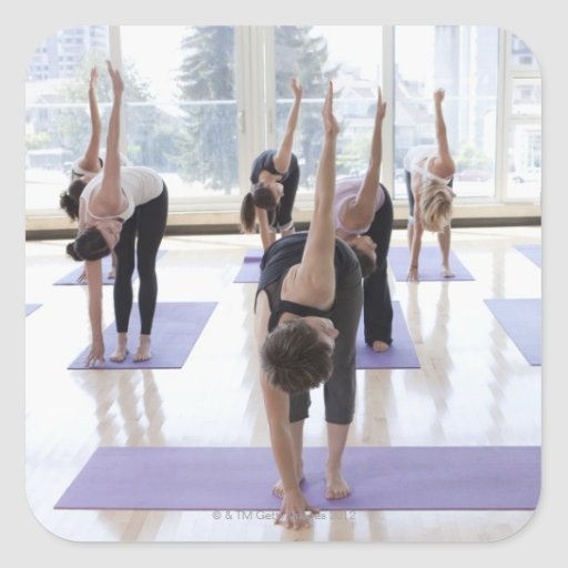 class practicing yoga with instructor in a sticker