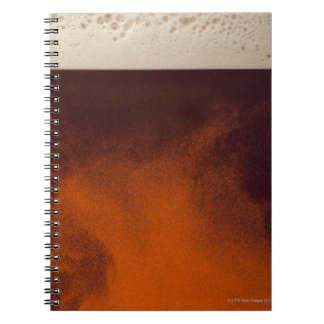 Close up image of amber colored beer with frothy spiral notebook