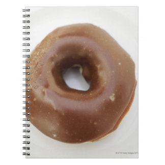 Close-up of a chocolate doughnut on a plate notebook