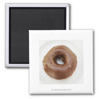 Close-up of a chocolate doughnut on a plate square magnet