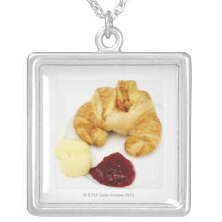 Close-up of a croissant served with butter and silver plated necklace