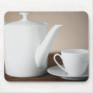 Close-up of a cup and a saucer with a tea kettle mouse mat