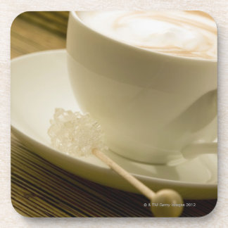 Close-up of a cup of coffee with a candy drink coaster