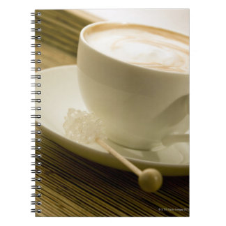 Close-up of a cup of coffee with a candy spiral notebook