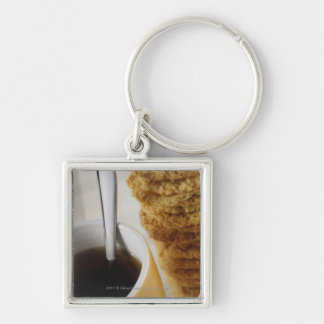 Close-up of a cup of coffee with cookies key ring