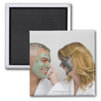 Close-up of a mature couple wearing facial masks refrigerator magnets