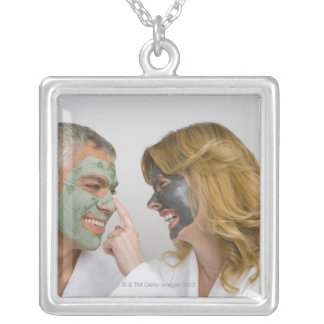 Close-up of a mature couple wearing facial masks silver plated necklace