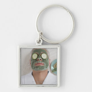 Close-up of a mature man lying down with a face keychain