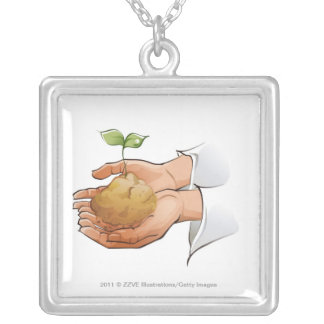Close-up of a person's hands holding seedling silver plated necklace