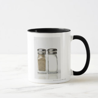 Close-up of a salt and a pepper shaker mug