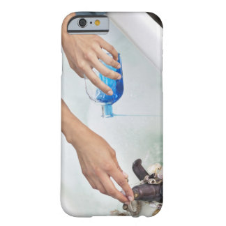 Close-up of a woman's hand pouring aromatherapy barely there iPhone 6 case